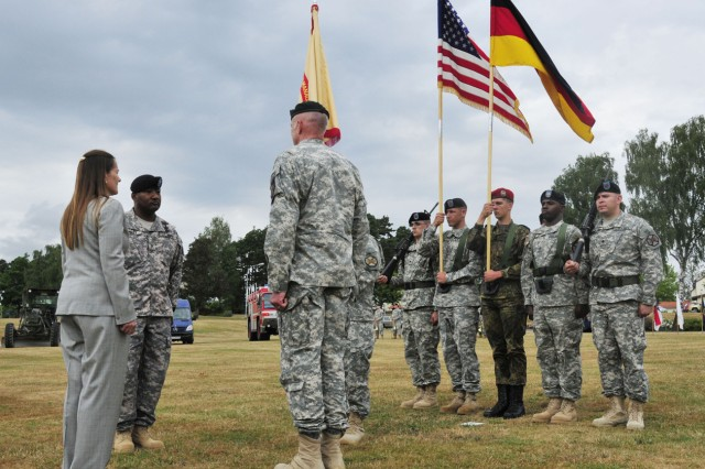 GRAFENWOEHR, Germany ― (From left to right) Diane Devens, director of Installation Management Command-Europe, incoming commander Col. Vann Smiley and outgoing commander Col. Chris Sorenson begin the passing of the colors during a change of command ceremony at the Main Post parade field, July 15.