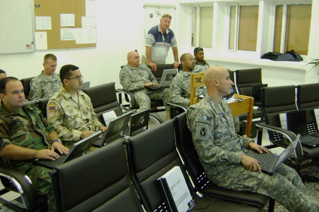 MC4's Ace Grigson (standing) teaches medical personnel from different nations to electronically chart patient care with the Army's MC4 systems while deployed in support of the Multinational Force and Observers mission on Egypt's Sinai