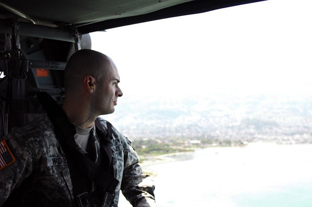 Capt. Jason Wood, 2009 Transportation Corps Regimental Officer of the Year, looks out the door of a UH-60 Black Hawk during a visit to SDDC personnel supporting Operation Unified Response in Haiti.
