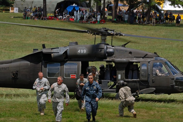 MUSCATATUCK URBAN TRAINING CENTER, Ind. - Adm. James Winnefeld Jr., commander of North American Aerospace Defense Command and U.S. Northern Command, exits a UH-60 Blackhawk helicopter with other key leaders July 16 to visit the Muscatatuck Urban Training Center in Butlerville, Ind. The leaders observed the training underway during the Vibrant Response 10.2 field training exercise, a national emergency response scenario aimed at preparing our first responders for the unthinkable - a nuclear blast in a major U.S. city. The exercise is facilitated by U.S. Army North's Joint Task Force - 51, headquartered in San Antonio.