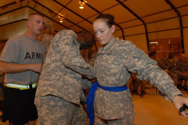 Spc. Sarah Lanphear, Headquarters and Headquarters Company, 3rd Brigade Special Troops Battalion, 3rd Heavy Brigade Combat Team, 3rd Infantry Division, gets some last minute advice while suiting up for her final match in the brigade's combatives tournament July 10 at Contingency Operating Site Kalsu, Iraq.  Winners will go on to represent 3rd HBCT and the 3rd Inf. Div. in the All-Army Combatives Tournament later this year.