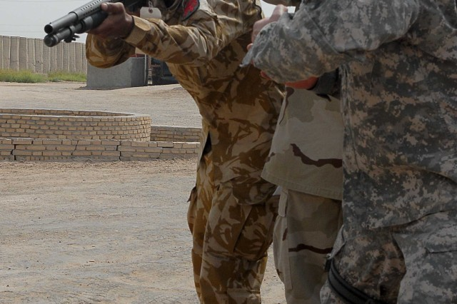Sgt. 1st Class Bryon Foreman, 354th Military Police Company operations sergeant from Tecumseh, Mich., shows a 14th Iraqi Army Division commando proper aiming techniques for a less-than-lethal round. The commandos received two days of instruction in crowd control techniques and less-than-lethal weaponry at their headquarters in Basra, Iraq, July 10-11.