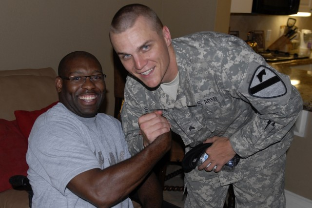 FORT HOOD, Texas - Sgt. Christopher Stevens (right), from Orlando, Fla., assigned to Company D, 1st Battalion, 12th Cavalry Regiment, 3rd Brigade Combat Team, 1st Cavalry Division, shares a laugh with Sgt. 1st Class Charles Armstead, a former platoon sergeant, during a brigade visit to Brooke Army Medical Center, in San Antonio, July 13.