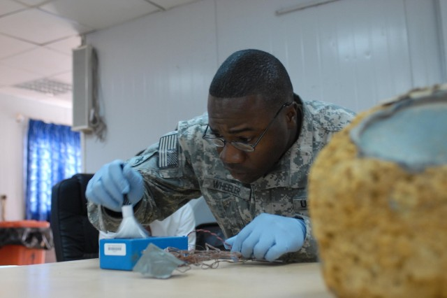 Spc. Victor Wheeler, a special weapons exploitation team member with the 663rd Ordinance Company, 3rd Brigade Combat Team, 4th Infantry Division and Ocala, Fla., native, dusts for fingerprints during a criminal investigation demonstration at a rule of law seminar. Attendees of the seminar discussed using evidence to prosecute suspects accused of employing explosive devices.