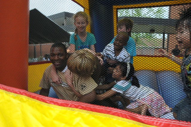 Spc. Caleb Henderson, Okeechobee, Fla., native and information systems analyst for the 3d Sustainment Command (Expeditionary), mobbed by children while in the inflatable castle at the 3d ESC's Family Day held at Pierce Elementary, Friday, July 9.  The Family Day served as a way to bring 3d ESC Soldiers, Families, and friends together for a day of fun. (U.S. Army photo by Sgt. 1st Class Dave Mcclain)