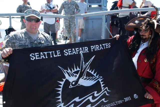 2nd Lt. Gregg Bergstrom, captain of the Army's LCM-8560, receives the Seafair Pirate flag from Captain Kidd XVI. The Army Reserve's 175th Transportation Company carried the pirates on their mission to storm Seattle's Alki Beach.