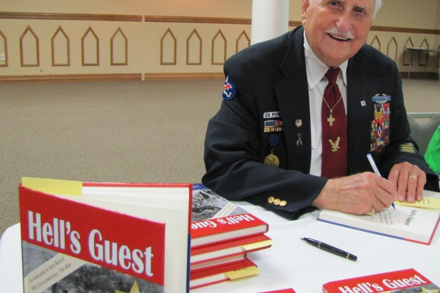 """Glenn Frazier, who survived the Bataan Death March, signs copies of his book """"Hell's Guest"""" at a meeting of the American Society of Military Comptrollers."""