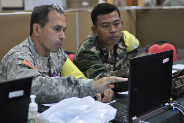 KUANTAN, Malaysia - U.S. Army Master Sgt. Runnel Klahr, intelligence non-commissioned officer in charge, U.S. Army Japan-Support Unit, 9th Mission Support Command, and Malaysian Army Capt. Zairol Bin Hj Zakario, troop leader, 11th Engineer Squadron, 3rd Infantry Division, lead the effort for the Request for Information Cell during the simulated combined post exercise as part of Keris Strike 2010.During the exercise, U.S. and Malaysian Armed Forces soldiers participate in academic training, a mini-staff exercise and a command post exercise. Participants also have a chance to further strengthen their relationships by competing in sporting events and enjoying cultural activities.