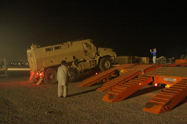 A Mine-Resistant Armor-Protected vehicle is loaded onto a civilian transport to be moved out of Iraq by contractors working under and escorted by Soldiers of the 1st Sustainment Brigade, based at Fort Riley, Kan., and deployed to Camp Arifjan, Kuwait.