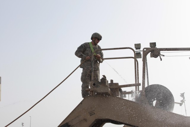 Sgt. Paul Vaughn, a Soldier with the 1st Sustainment Brigade, based at Fort Riley, Kan., and deployed to Camp Arifjan, Kuwait, washes a military transport after the first Durable Express convoy, May 15-22, 2010.  The Durable Express is 1st SB's answer to the challenge of moving some two million pieces out of Iraq as part of the U.S. drawdown of forces.