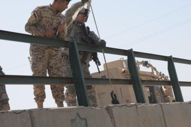 Staff Sgt. Bowman McArthur, 1st Battalion, 8th Infantry Regiment, 3rd Brigade Combat Team, 4th Infantry Division, and his Iraqi Army counterpart record bridge data to help assess the feasibility of a new route between Maysan and Dhi Qar during Operation Road Dog.
