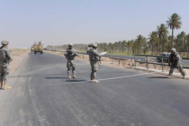 Soldiers from 1st Battalion, 8th Infantry Regiment, 3rd Brigade Combat Team, 4th Infantry Division measure the width of a road along a route during Operation Road Dog.  The newly cleared and classified route could be used by both military and civilian traffic and will likely boost economic development in southern Iraq