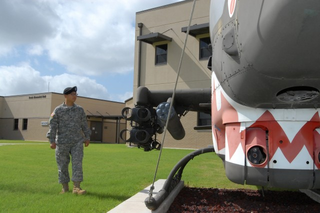 "FORT HOOD, Texas - Spc. Cecil Wong, from Dallas, a paralegal specialist for 1st Air Cavalry Brigade, 1st Cavalry Division, looks at a Cobra helicopter as he takes in his new surroundings at the 1st ACB headquarters building, here, July 15. Wong immigrated to the U.S. from Hong Kong with his wife, 14 months ago and he quickly fulfilled his lifelong dream of joining the Army. ""I am really a member of the very best team,"" said Wong."
