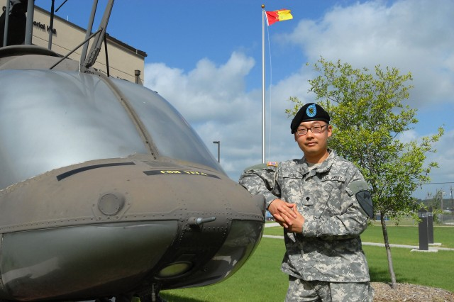 FORT HOOD, Texas - Spc. Cecil Wong, from Dallas, a paralegal specialist for 1st Air Cavalry Brigade, 1st Cavalry Division, pauses next to a Kiowa helicopter in front of the 1st ACB's headquarters building, here, July 15. Wong, who recently immigrated to the U.S. with his wife has been in the Army for nine out of the 14 months he has been in the U.S.