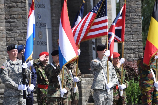 CHIEVRES, Belgium -- A multinational color guard from NATO military base Supreme Headquarters Allied Powers Europe parades Allied colors in front of the Mardasson Memorial July 16 near Bastogne, Belgium.