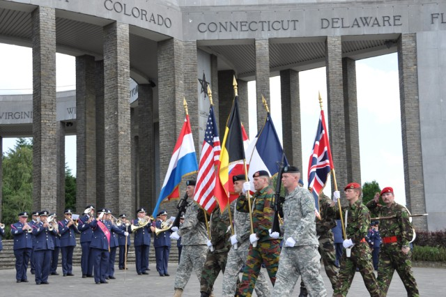 CHIEVRES, Belgium -- A multinational color guard from NATO military base Supreme Headquarters Allied Powers Europe in Mons, Belgium, parades Allied colors in front of the Mardasson Memorial July 16.