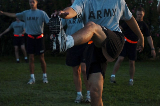 U.S. Army Cadet Robert Thompson, an electrical engineer major, performs a series of warm-up exercises prior to a physical fitness training session with 25th Infantry Division senior leadership at Sills Field on Schofield Barracks, Hawaii, July 20. The cadets were invited with their sponsors to the division to meet division leadership and experience a day in the life of a Tropic Lightning Soldier. (U.S. Army photo by Spc. Jesus J. Aranda, 25th Infantry Division Public Affairs Office)