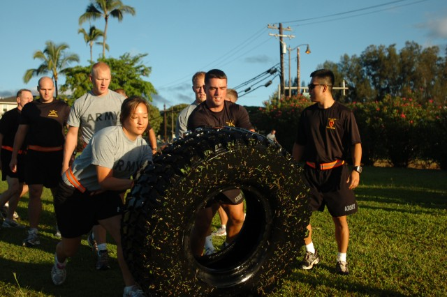 U.S. Army cadets and their sponsors work together to flip a large tire during a physical fitness training session with 25th Infantry Division senior leadership at Sills Field on Schofield Barracks, Hawaii, July 20. The cadets and their sponsors were challenged to a series of physical trials during the morning's training session alongside division's leadership. (U.S. Army photo by Spc. Jesus J. Aranda, 25th Infantry Division Public Affairs Office)