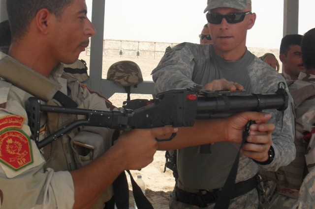 Spc. John Bosecker shows a member of the Iraqi Army how to properly use non-lethal weapons in riot control at Contingency Operating Base Basra July 15.  Bosecker is a member of the 354th Military Police Company out of St. Louis.