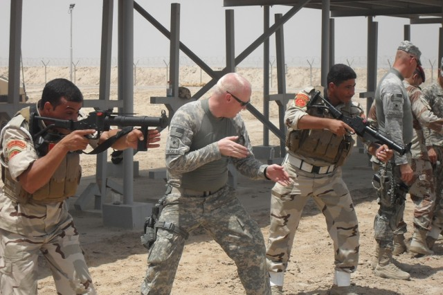 Spc. Michael Rogers of the 354th Military Police Company teaches riot control techniques to members of the Iraqi Army at Contingency Operating Base Basra July 15.