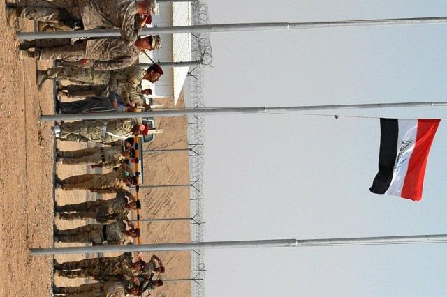 Members of the Iraqi Marine Detachment at Camp Bucca raise the Iraqi flag over the former Theater Internment Facility as part of the base's transfer ceremony July 11. Moments earlier, U. S. Marines lowered the American flag posted at the facility.