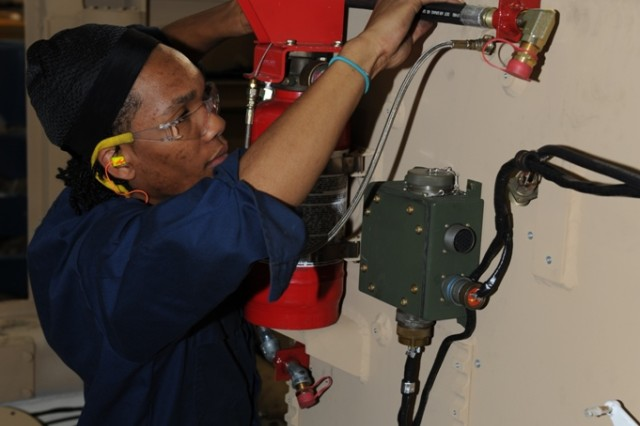 Myrone Houston connects hoses for the fire extinguisher on the M9ACE at Anniston Army Depot.