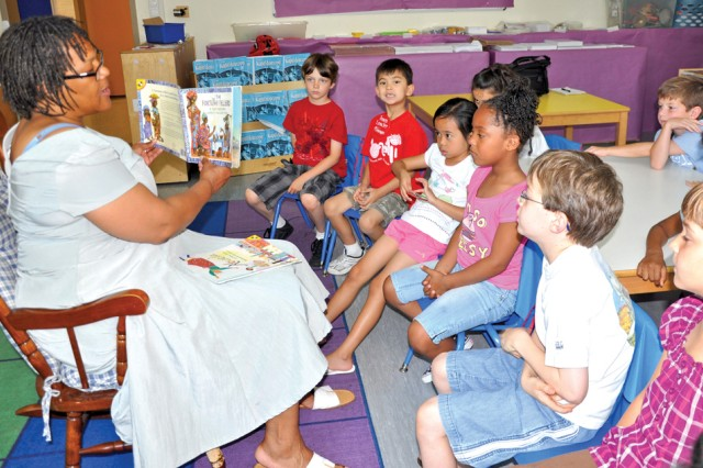 "LaVera Long reads ""The Fortune Teller"" to a mixed class of kindergartners and first-graders during the Wiesbaden Summer Enrichment Program."