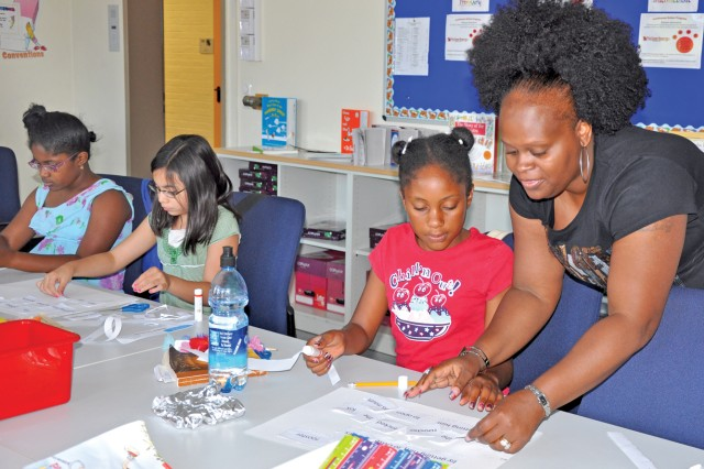 Vanessa Brown encourages Makyla Jones and other students in an activity to unscramble sentences.