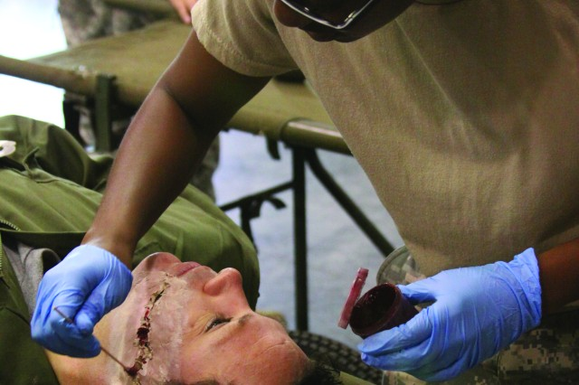 Pfc. Natasha Mitchelle, a medical logistics specialist, applies makeup on Pfc. Greg Newton, an X-ray technician, both with the 345th Combat Support Hospital, to simulate a gunshot wound across the face for other medics in the field to assess and treat at Fort Gordon, Ga., during the Global Medic 2010 training exercise July 15-19.