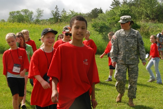 Issac R. Coutier, left, 10, from Bloomington, Minn. leads a column of campers while Staff Sgt. Charreise U. Lewandowski, right, human resources noncommissioned officer with the 372nd Engineer Battalion, calls cadence to keep the campers in marching step in the course of drill and ceremony during Military Day at an Army Reserve Youth Enrichment Camp on June 16, 2010 at at Camp Ihduhapi, Minn.