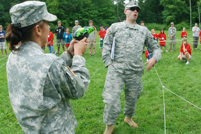 Sgt. Ivy N. Toogood, noncommissioned officer of fun, shoots Master Sgt. Joseph J. Devine, noncommissioned officer in charge of fun, as they demonstrate the fun roles of engagement during Military Day at an Army Reserve Youth Enrichment Camp on June 16, 2010 at at Camp Ihduhapi, Minn. Both Soldiers are assigned to the 88th Regional Support Command's Soldier Readiness Processing Detachment.