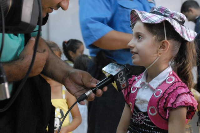 A young girl from Nasiriyah is interviewed by local media after an Iraqi Police criminal investigation course graduation at the Mittica Training Center.