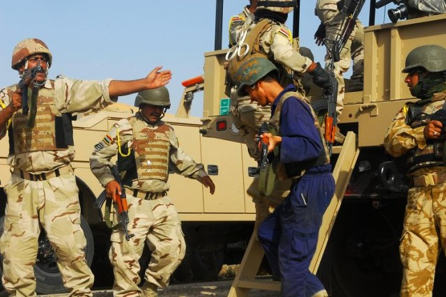 Soldiers with 32nd Company, 8th Iraqi Army Division Transportation Directorate load into their vehicles after establishing a security perimeter during urban operations training in Numaniyah July 14.
