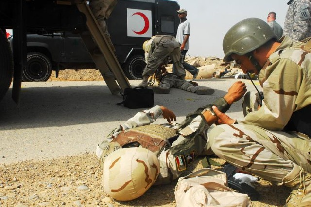 """A soldier with 32nd Company, 8th Iraqi Army Division Transportation Directorate provides first aid to a simulated casualty after an improvised explosive device attack during urban operations training in Numaniyah, July 14. The wounded were rushed from the """"kill zone"""" to a nearby medical facility that participated in the exercise."""