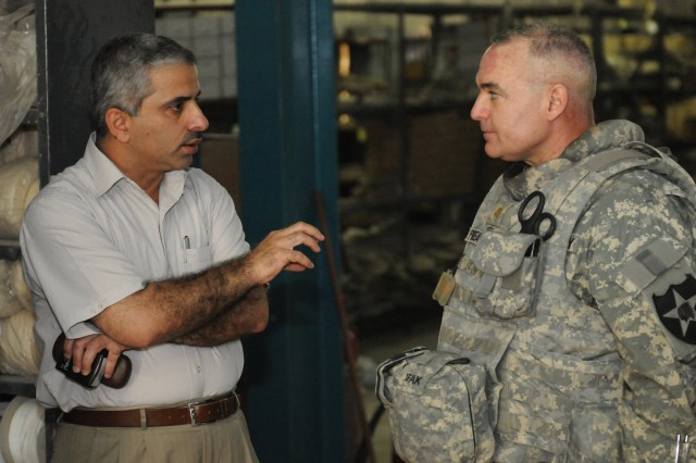 The director of physical therapy at Adamiyah Hospital, Dr. Emad Khudair, speaks to Maj. Michael Perreault, brigade surgeon for 4th Stryker Brigade Combat Team, 2nd Infantry Division, U.S. Division-Center, during a delivery of prosthetic limbs. The delivery helps the hospital better serve the more than 400 patients who cycle through the physical therapy department.