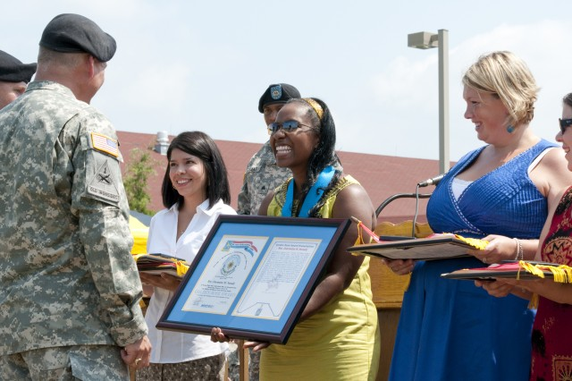 Charmaine Nunally, center, wife of Capt. Joshua Nunnally, 319th Military Intelligence Battalion, receives the Golden Rose award from Col. James D. Edwards, 525th Battlefield Surveillance Brigade commander, for her 400 hours of volunteer service to the 319th MI Bn. Friday at the 525th BFSB Deployment Ceremony.