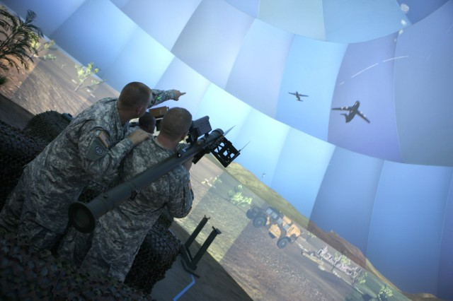 Spc. Steven Tharpe and Pvt. Ricky Hammons point at virtual enemy aircraft inside the new Joint Fires Multipurpose Dome July 15. It is part of their Advanced Individual Training to become Air and Missile Defense Crewmembers.