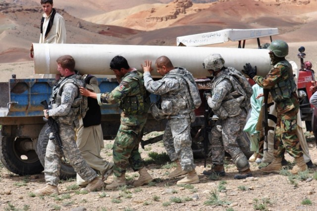 Captain Douglas Gray (front), civil affairs officer in charge, Headquarters and Headquarters Company, Task Force Brawler, 3rd Combat Aviation Brigade, TF Falcon, from Ojai, Calif., leads other Brawlers and their Afghan National Army partners in the loading of a roll of carpet onto a waiting farmer's tractor in the Logar province, Afghanistan, April 22. The carpet was brought as part of a mosque refurbishment project started by Gray and his S-9 team.
