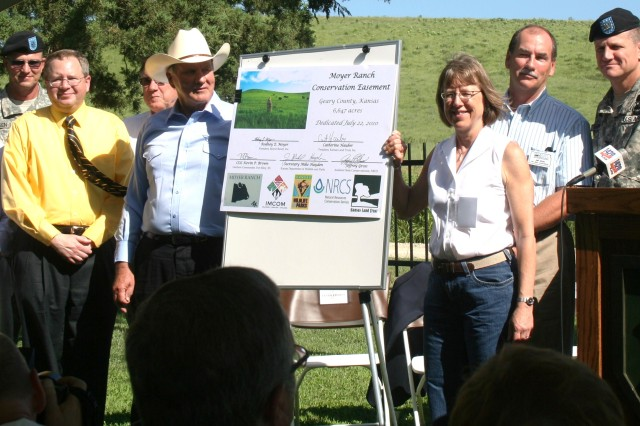 FORT RILEY, Kan. - Rodney Moyer, president of Moyer Ranch, Inc., and Catherine Hauber, president of Kansas Land Trust, Inc., stand next to a signed agreement dedicating 6,647 acres of land to a conservation easement, July 22 at the Moyer Ranch near Fort Riley, Kan. By signing the conservation easement agreement, Moyer agreed to suspend any future development of that land. Also signing the agreement were: Sec. Mike Hayden, Kansas Department of Wildlife and Parks, Jeffrey Gross, assistant state conservationist with the Natural Resources Conservation Service, and Col. Kevin P. Brown, Fort Riley garrison commander.