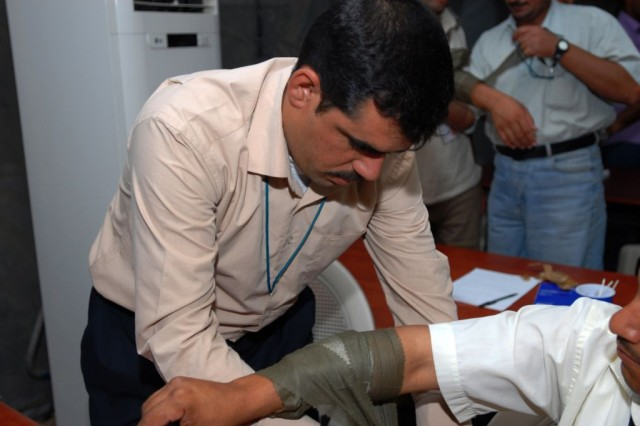 Sgt. Aqael Hadi Kianbr, a police officer from Babil Province, Iraq, practices applying a tourniquet July 19 during the second day of medical classes taught to local Iraqi Police at Contingency Operating Site Kalsu by the 253rd Military Police Company out of Lenoir City, Tenn.