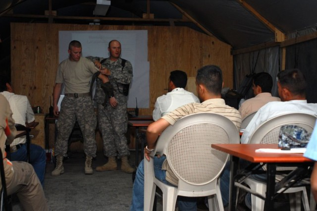 Staff Sgt. Rick Mackneer from New Bern, N.C., the Combat Life-saver course instructor and medical noncommissioned officer in charge for the 253rd Military Police Company out of Lenoir City, Tenn., instructs Iraqi Police officers from the Babil Province on how to apply a tourniquet July 19 with the help of his demonstrator, Pfc. Kevin Marlin from Murfreesboro, Tenn., also assigned to the 253rd MP Co.