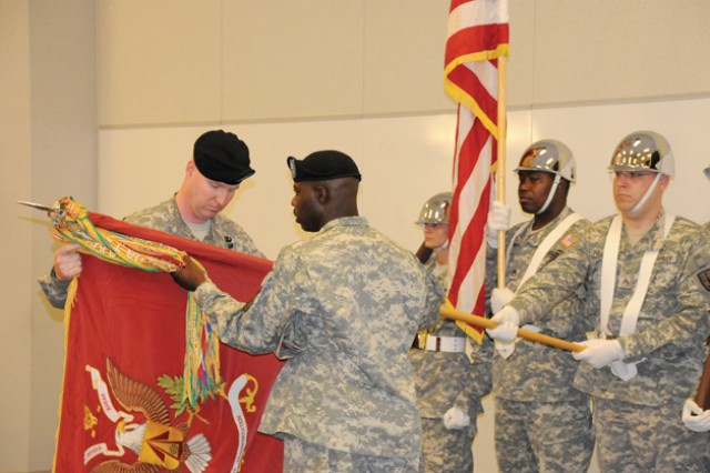 Lt. Col. Timothy M. Gilhool, outgoing 71st Transportation Battalion commander, uncases the battalion guidon during a ceremony Friday with the assistance of 1st Sgt. Teon M. Wright, acting command sergeant major for the unit. The uncasing of the unit's guidon was the duo's last act while in charge of the unit.