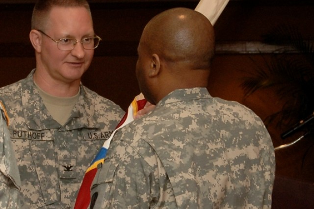 The new Commander of the 411th CSB, Frederick A. Puthoff passes the colors to his Senior Enlisted Advisor, SGM Jesse T. Hammond.
