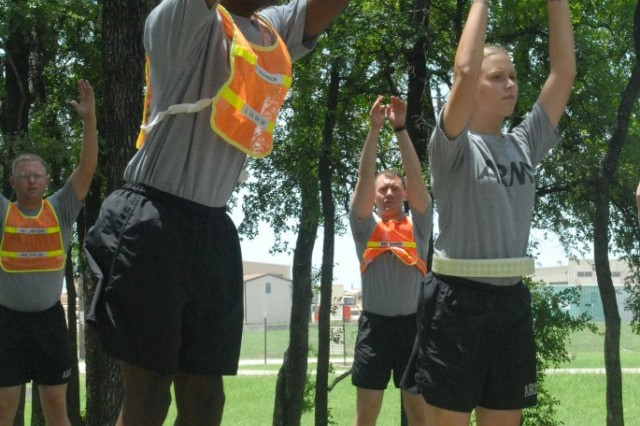 FORT HOOD, Texas -- Parkersburg, W.V. native, Spc. Jessica Samuels (right), the Building Soldier Athletes class instructor, assists Sgt. Williamson, in performing a warm-up exercise known as the high jumper during the eight-day class, here, July 13.