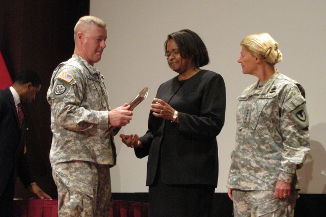 The Army Materiel Command's Command Sgt. Maj. Jeffrey Mellinger and commander Gen. Ann Dunwoody present AMCOM G-1 acting director Lori Reynolds with the Louis Dellamonica Award for Outstanding Performance.