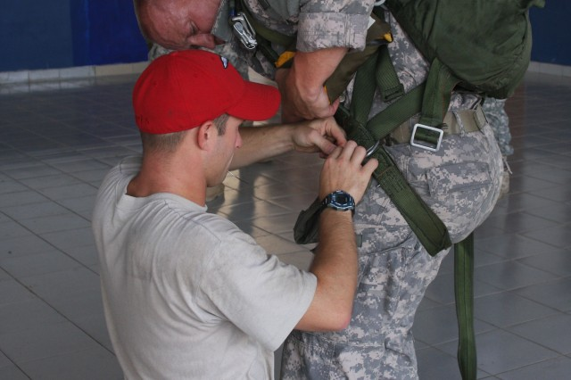 KAMPONG SPEU, Cambodia - Staff Sgt. Gregory Haskell, a food service specialist with 197th Special Troops Company (Airborne), watches as a rigger from 1st Battalion, 1st Special Forces Group fixes his parachute harness during the friendship jump for Angkor Sentinel 2010.   Angkor Sentinel is a multinational training exercise supporting peace support operations co-sponsored by the Royal Cambodian Armed Forces, U.S. Pacific Command and U.S. Army Pacific.