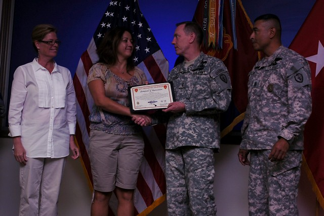 "Amy Buck, spouse of a Soldier from Company C, 1st Battalion, 14th Infantry Regiment, 25th Infantry Division, receives a Military Spouse Tropic Lightning ""Ali'i Award"" for serving as a key volunteer for the unit's Family Readiness Group, from Maj. Gen. Bernard S. Champoux, commanding general, 25th Inf. Div., during the 25th Inf. Div. Quarterly Volunteer Awards and Recognition Ceremony July 23 at the Main Post Conference Room, Schofield Barracks, Hawaii. The ceremony was held to recognize and honor the men and women volunteers who give selflessly of their time and energy throughout our community."