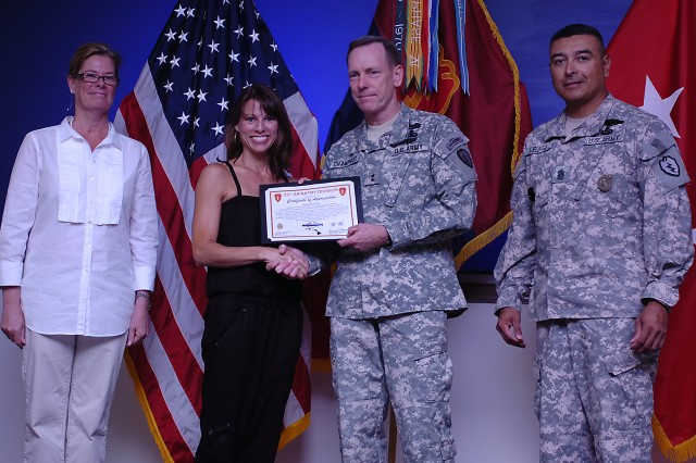"Melissa Gardner, spouse of a Soldier from Headquarters and Headquarters Company, 3rd Battalion, 25th Aviation Regiment, 25th Infantry Division, receives a Volunteer Ambassador Award ""Lokahi"" for serving as the treasurer and senior advisor for the Family Readiness Group, from Maj. Gen. Bernard S. Champoux, commanding general, 25th Inf. Div., during the 25th Inf. Div. Quarterly Volunteer Awards and Recognition Ceremony, July 23 at the Main Post Conference Room, Schofield Barracks, Hawaii. The ceremony was held to recognize and honor the men and women volunteers who give selflessly of their time and energy throughout our community."
