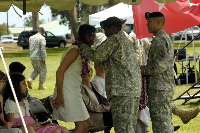 """Mrs. Theresa LaCamera, wife of the incoming 25th Infantry Division deputy commanding general - operations, Brig. Gen. Paul J. LaCamera, is welcomed to the division with a Hawaiian lei from Capt. Hope Woods, Headquarters and Headquarters Battalion, 25th Inf. Div. during a """"Flying V Ceremony"""" on Sills Field at Schofield Barracks, Hawaii, July 23. The ceremony welcomed incoming division leaders and their families in preparation for the division's upcoming deployment to Baghdad later this year. (U.S. Army photo by Spc. Jesus J. Aranda, 25th Infantry Division Public Affairs)"""