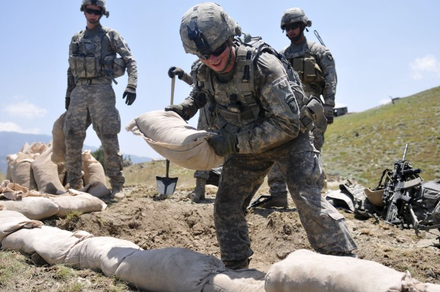 Pfc. David W. Wilson, of Salisbury, N.C., a grenadier with 2nd Battalion, 327th Infantry Regiment, stacks sandbags in an effort to improve a fighting position at Combat Outpost Thomas above the Marawarah District in Afghanistan's Kunar province, July 7. The Soldiers continuously work to improve their fighting positions while ever mindful of the extreme weather conditions that surpass 100 degrees daily.